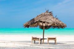 两把轻便折叠躺椅和伞在热带海滩 库存照片