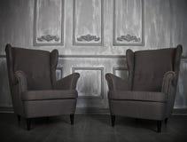 两把经典扶手椅子对一个灰色墙壁和地板 免版税图库摄影