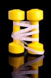 两把黄色哑铃和卷尺垂直安置与ref 库存照片