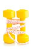 两把黄色哑铃和卷尺安置了垂直隔绝 免版税图库摄影