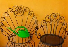 两把黑铁椅子和一个绿色喷壶在大放置了 免版税图库摄影