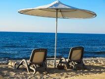 两把deckchairs和伞在蓝色海沙海滩 免版税库存图片