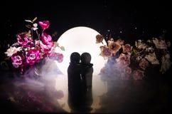两拥抱在与花和月亮装饰的桌上的玩偶点燃了与烟的背景 概念亲吻妇女的爱人 问候或礼品券desig 免版税图库摄影