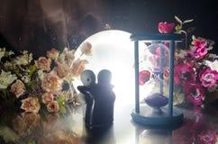 两拥抱在与花和月亮装饰的桌上的玩偶点燃了与烟的背景 概念亲吻妇女的爱人 问候或礼品券desig 免版税库存照片