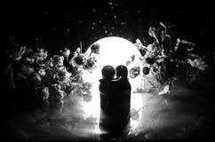 两拥抱在与花和月亮装饰的桌上的玩偶点燃了与烟的背景 概念亲吻妇女的爱人 问候或礼品券desig 库存图片