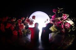 两拥抱在与花和月亮装饰的桌上的玩偶点燃了与烟的背景 概念亲吻妇女的爱人 问候或礼品券desig 免版税库存图片