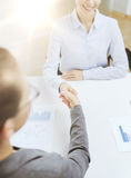 两握手的微笑的女实业家在办公室 免版税图库摄影