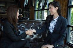 两握手的确信的亚裔女商人在一次会议期间在办公室 免版税库存照片