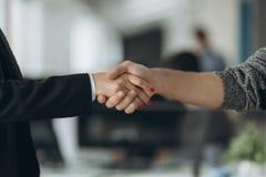 两握手的确信的商人在一次会议期间在办公室,成功,成交,问候和伙伴概念 免版税库存图片