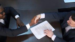 两握手的确信的商人在一次会议期间在办公室 库存照片