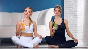 两摆在与新鲜的维生素鸡尾酒坐的莲花姿势的健身妇女在瑜伽班演播室 股票录像
