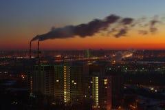 两支工业管,日出城市视图,桃红色温暖的天空 免版税库存照片
