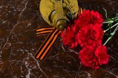 两支康乃馨,一个军用烧瓶和圣乔治丝带,以纪念碑为背景 免版税库存照片