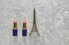 两支桃红色唇膏和埃佛尔铁塔的小雕象在灰色具体背景的 顶视图 免版税图库摄影