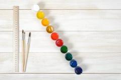 两支画笔和厘米统治者顶视图与五颜六色的树胶水彩画颜料容器在木背景 免版税库存图片