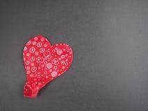 两放气了形成心脏的红色气球 库存图片