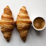 两新月形面包和浓咖啡在白色背景 免版税库存图片