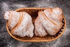 两新月形面包洒与在一个柳条筐的搽粉的糖在黑石背景特写镜头 顶视图 库存照片