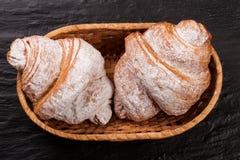 两新月形面包洒与在一个柳条筐的搽粉的糖在黑石背景特写镜头 顶视图 免版税库存照片