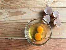 两新鲜的卵黄质和蛋白在玻璃杯子和蛋壳 图库摄影