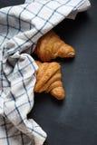 两新鲜的新月形面包和扭转的毛巾 库存照片