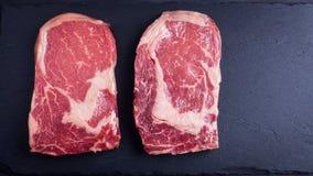 两新鲜的未加工的大理石肉,在黑暗的石背景的黑安格斯ribeye牛排 库存图片