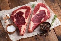 两新鲜的未加工的大理石肉,黑安格斯ribeye牛排用在一张老土气桌上的香料 在木背景的未加工的牛肉 顶视图 免版税库存照片