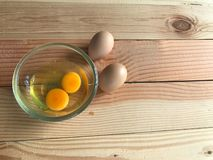 两新鲜的鸡卵黄质和蛋白在玻璃杯子和另外两个鸡蛋 免版税库存图片
