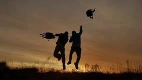 两旅游人跑的跳跃滑稽和投掷挑运剪影在日落阳光 两个人跳跃滑稽 影视素材