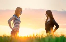 两日落的美丽的女孩有争论在自然 免版税库存照片