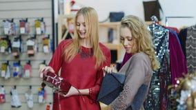 两时髦的夫人在辅助部件商店和衣裳选择提包 购物成功 股票录像