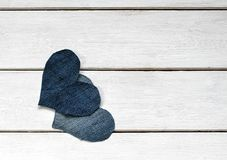 两时髦的心脏从一起说谎在wh的蓝色牛仔布被削减 免版税图库摄影