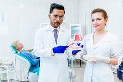 两显示下颌模型的牙医在诊所 免版税库存照片