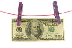 两晒衣夹的一百美元在绳子 免版税库存图片