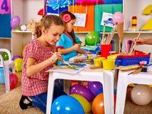 两有刷子绘画的小女孩在幼儿园 库存图片