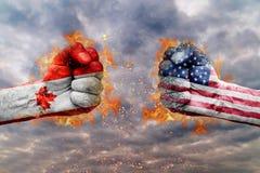 两有加拿大和美国的旗子的拳头面对在彼此 图库摄影