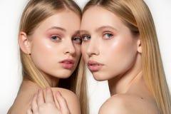 两有摆在魅力构成的白肤金发的长发的性感的可爱的孪生妇女,在彼此后的替换者,摆在 免版税库存照片