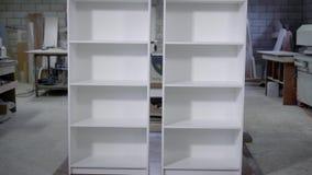 两有架子的白色完成的碗柜在木匠业站立,垂直的全景车间  股票录像
