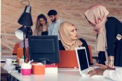 两有研究膝上型计算机的hijab的妇女在办公室 免版税库存图片