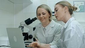 两有膝上型计算机和一个显微镜的年轻化验员在实验室里 股票录像