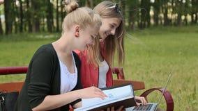两有膝上型计算机的年轻美丽的女学生在手中在一条长凳在绿色公园 研究 讨论 侧视图 股票视频