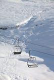 两有随风飘飞的雪的驾空滑车和滑雪场地外的倾斜在太阳早晨 免版税库存照片