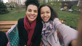 两有购物袋的快乐的混合的族种妇女谈话在与smartpone的录影电话 女孩坐长凳有 股票录像