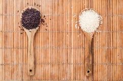 两木头匙子用胡椒和盐在竹背景 免版税库存照片