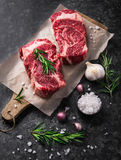 两未加工的新使有大理石花纹的肉黑色安格斯牛排ribeye,大蒜,盐 库存图片