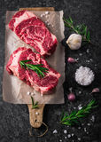 两未加工的新使有大理石花纹的肉黑色安格斯牛排ribeye,大蒜,盐 图库摄影