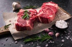 两未加工的新使有大理石花纹的肉黑色安格斯牛排ribeye,大蒜,盐 免版税库存照片