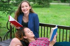 两本十几岁的女孩阅读书在公园 库存照片