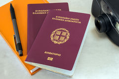 两本护照、照相机和橙色笔记本 库存图片