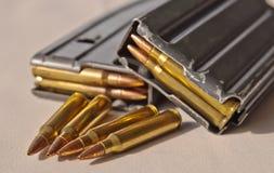 两本金属步枪杂志,一堆积了在其他,装载与 223枚口径子弹用四枚另外的子弹 免版税库存图片